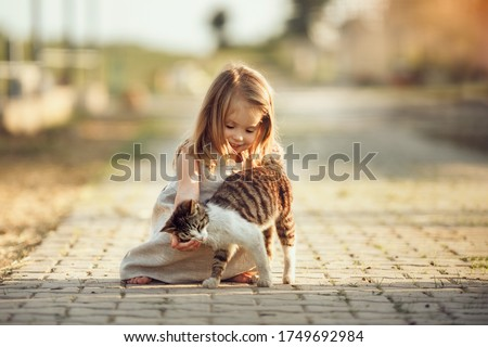 A little barefooted girl in a gray linen dress is stroking a cat. Sunny summer evening in the village. Countryside background. Image with selective focus, toning and noise effects. Stock photo ©