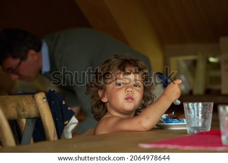 A little beautiful curly-haired girl is eating in the kitchen. Dad's making breakfast. He looks at the camera. Furniture made of natural wood.