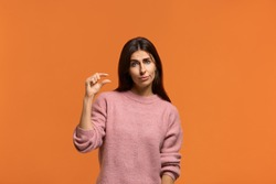 A little bit. Beautiful woman shows little bit gesture, asks some more, please give me few more. shows that this is insignificant. wears in pink knitted sweater isolated over orange background