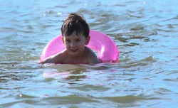 A little black-haired cute boy with a pink life buoy is swimming in the sea. closeup, summer, beautiful happy kid swims in the river.