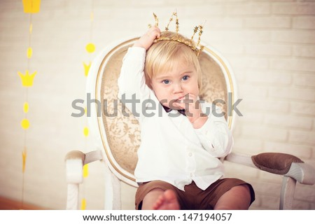 a little blond boy sitting on a chair, on his head a crown, eat cookies ストックフォト ©