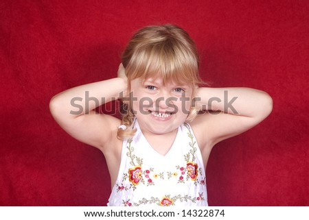 A little blond girl acting silly - hands on ears