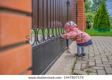 A little blond girl peers out through the bars of the gate. A happy curious baby is exploring the world with interest #1447807574