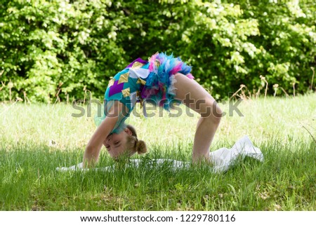 Stock Photo A little blonde girl doing a yoga backbend wheel pose on a green grass. Stretching and fitness training on the summer meadow, healthy childhood
