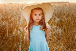 A little blonde girl in a blue dress and a very big mother's hat on a wheat field at sunset. Portrait of a child against the background of rye ears.