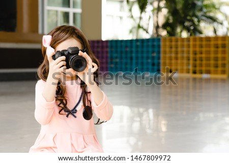 A little blonde girl photographer is taking a photo. Model isolated on a ground with copy space.Concept : Back to school and education.