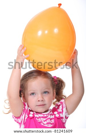 a little blonde girl playing with a balloon