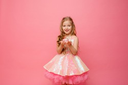 a little blonde girl with long hair holds a birthday cake with a candle on a pink background