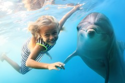 A little blonde seven year old girl diving with funny dolphins underwater. An ocean life sports extreme design. Kid with marine animal. Red sea diving in blue water.