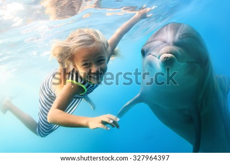 Stock Photo A little blonde seven year old girl diving with funny dolphins underwater. An ocean life sports extreme design. Kid with marine animal. Red sea diving in blue water.