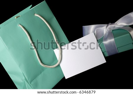 A little blue bag with matching gift and blank white gift card for your message. - stock photo