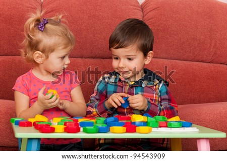 A little boy and a little girl are playing at the table