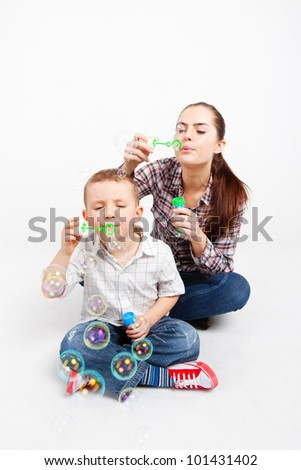 A little boy and a pretty woman sit cross-legged on the floor and let go soap bubbles.