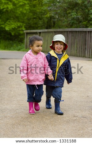 A little boy and girl wearing wellington boots holding hands and walking through a country park