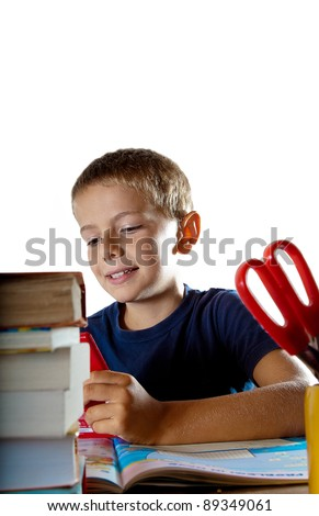 A little boy at work on his homework on his tablet computer nd a smile on his face, getting ready to go back to school. Isolated on white background with plenty of copyspace.