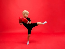 a little boy boxer stands sideways in red boxing gloves and makes a kick on a red background with space for text