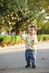 A little boy chasing bubbles and playing