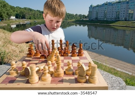A little boy chess with river at background