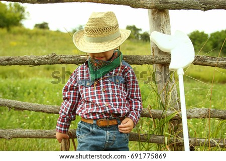 a little boy cowboy on nature #691775869