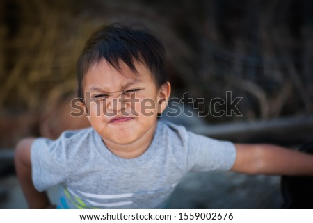 A little boy expressing resentful and uncooperative attitude by making an upset face and confontational body stance. #1559002676