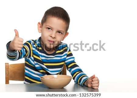 A little boy has breakfast at the table