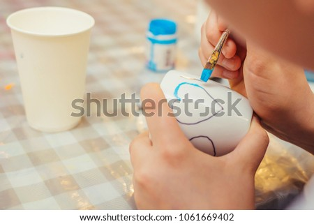 A little boy holding a brush in his hands and decorating a cup. And he draws a heart with a blue paint. Drawing lesson. Drawing process closeup. #1061669402