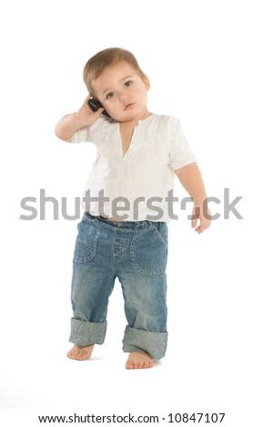 A little boy holding a cellphone near his ear - stock photo