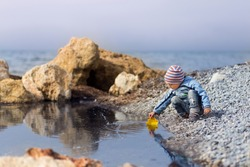 A little boy in a blue jacket and striped hat sits by the sea on a wild beach. A little boy scoops up water with a plastic mold in the form of a boat. Image with a selective focus