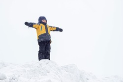 A little boy in a yellow jacket stands on top of a mountain with his hands up in the winter. The child imagines that he is flying like a bird. The conqueror of the peaks