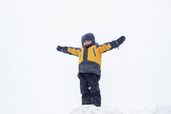 A little boy in a yellow jacket stands on top of a snowy mountain with his hands up in the winter. The child imagines that he is flying like a bird. The conqueror of the peaks