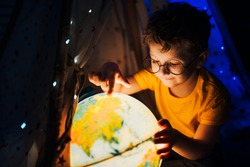 A little boy in glasses sits at night in a tent and plays with a globe.