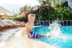 A little boy in striped shorts splashing feet in the pool next to the hotel, wrinkling his nose from the sun. Summer vacation. Vacation.
