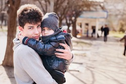 A little boy in the arms of his older brother rest after a long walk in the spring and feels safe in hugs. An elder brother loves to walk with his younger brother and take care of him