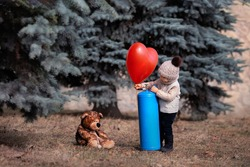 A little boy inflates a balloon with helium. Baby and his friend bear in the park. Winnie the Pooh. Spring walk of a child with a toy. Childhood. Based on a fairy tale. helium tank