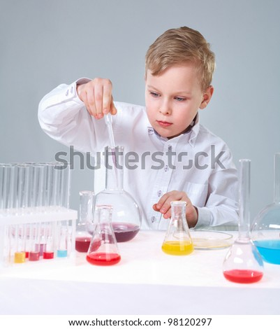 A little boy injuring liquid into a flask and looking at it