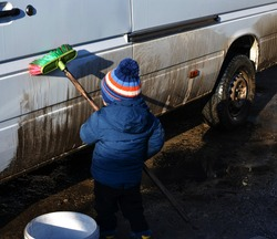 A little boy is cleaning a dirty car with a brush. The concept of child labor, and oppression. Use of child labour.
