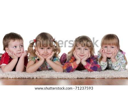 A little boy is lying at three smiling girls; isolated on the white background