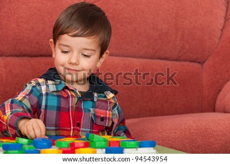 A little boy is playing at the table