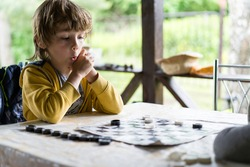 a little boy is playing checkers at a table on the summer porch