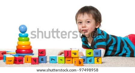 A little boy is playing with blocks on the carpet; isolated on the white background