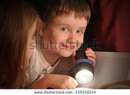 A little boy is reading a book at night with a flashlight in his bedroom for an education or fairytale concept.