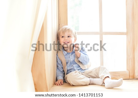 A little boy is sitting on the windowsill in the nursery. The concept of leisure, leisure, people and lifestyle. Portrait of a smiling boy sitting on a wooden window sill, looking at the camera. #1413701153