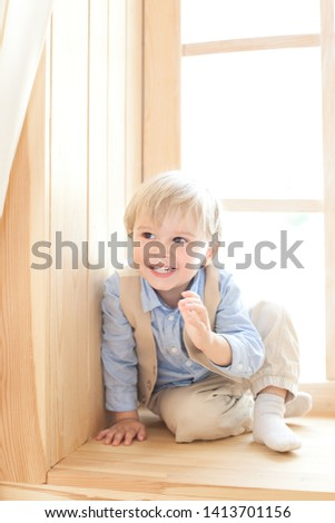 A little boy is sitting on the windowsill in the nursery. The concept of leisure, leisure, people and lifestyle. Portrait of a smiling boy sitting on a wooden window sill, looking at the camera. #1413701156