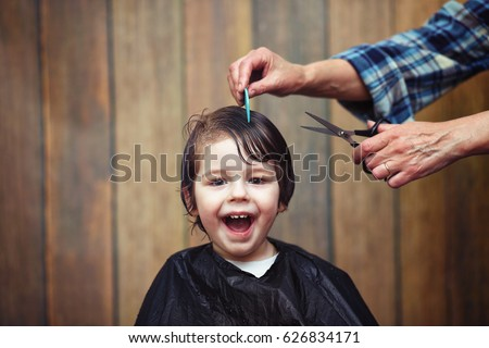 A little boy is trimmed in the hairdresser's bright emotions on his face