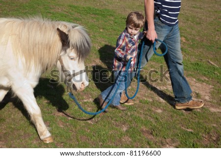 A little boy leading a pony while holding his father's hand