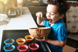 A little boy licks a spoon with chocolate dough. Time with the kids at home. Little chef. Child in the kitchen. Cooking baked goods with children. Boy preparing cupcakes from ready mix