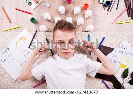 A little boy lies among the markers and drawings of LED bulbs #629410679