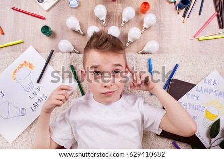 A little boy lies among the markers and drawings of LED bulbs #629410682