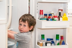 A little boy looking for something sweet in the refridgerator.