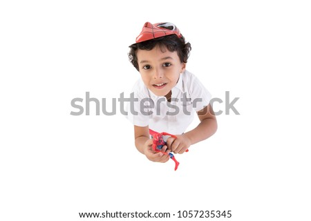 A little boy looking up, above shot wearing spiderman mask putting it on his head, isolated on a white background.